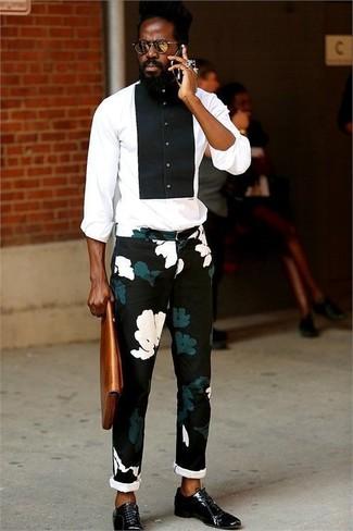 Cómo combinar: camisa de vestir en blanco y negro, pantalón chino con print de flores negro, zapatos oxford de cuero negros, bolso con cremallera de cuero en tabaco