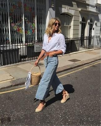 Cómo combinar: camisa de vestir de lino blanca, falda pantalón vaquera celeste, sandalias con cuña de lona en beige, cartera sobre de paja marrón claro