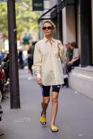 Cómo combinar: camisa de vestir amarilla, mallas ciclistas estampadas negras, sandalias planas de goma amarillas, bolsa tote de goma transparente
