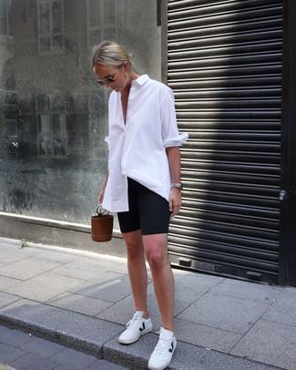 Cómo combinar: camisa de vestir blanca, mallas ciclistas negras, tenis de cuero blancos, mochila con cordón de cuero marrón