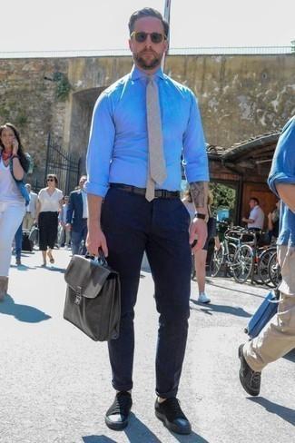 Una camisa de vestir de vestir con un pantalón chino azul marino: Haz de una camisa de vestir y un pantalón chino azul marino tu atuendo para un lindo look para el trabajo. Si no quieres vestir totalmente formal, usa un par de tenis de lona negros.