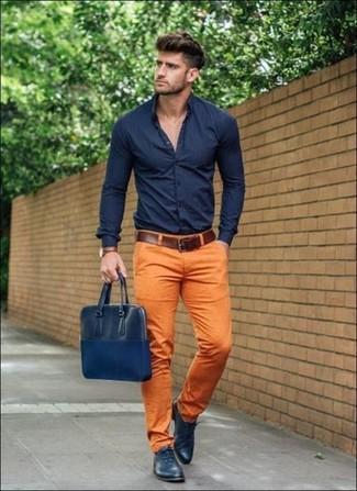Cómo combinar: camisa de vestir azul marino, pantalón chino naranja, zapatos oxford de cuero azul marino, bolso mensajero de cuero azul marino
