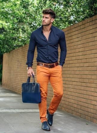 Cómo combinar: camisa de vestir azul marino, pantalón chino naranja, zapatos oxford de cuero azul marino, portafolio de cuero azul marino