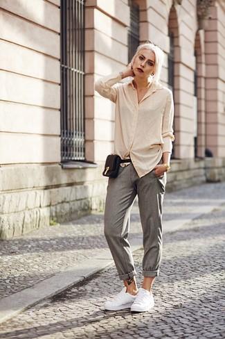 Cómo combinar: camisa de vestir en beige, pantalón de pinzas gris, tenis de cuero blancos, riñonera de cuero negra