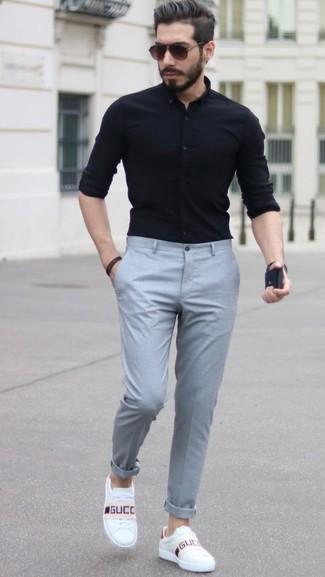 Cómo combinar: camisa de vestir negra, pantalón de vestir gris, tenis de cuero blancos, gafas de sol en marrón oscuro
