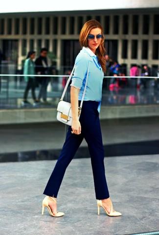 Cómo combinar: camisa de vestir celeste, pantalón de vestir azul marino, zapatos de tacón de cuero en beige, bolso bandolera de cuero blanco