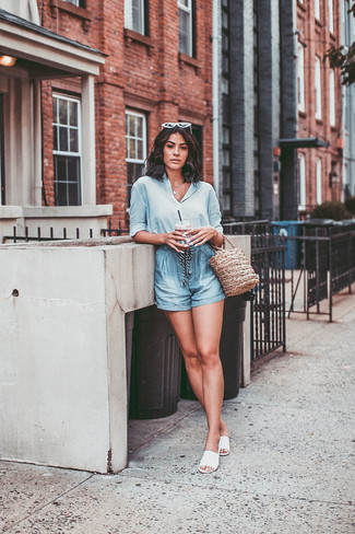 Cómo combinar: camisa de vestir de seda celeste, pantalones cortos celestes, sandalias planas de cuero blancas, mochila con cordón de paja marrón claro