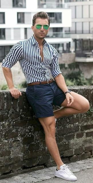 Haz de una camisa de vestir de rayas verticales en blanco y azul marino y unos pantalones cortos azul marino tu atuendo para las 8 horas. ¿Te sientes valiente? Completa tu atuendo con tenis blancos.