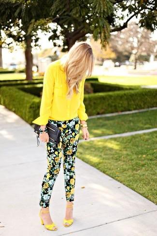 Cómo combinar: camisa de vestir de gasa amarilla, pantalones pitillo con print de flores negros, sandalias de tacón de cuero amarillas, cartera sobre de cuero negra