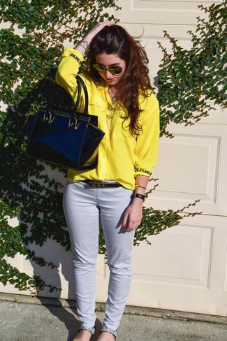 Cómo combinar: camisa de vestir amarilla, pantalones pitillo blancos, sandalias planas de cuero con print de serpiente grises, bolsa tote de cuero negra