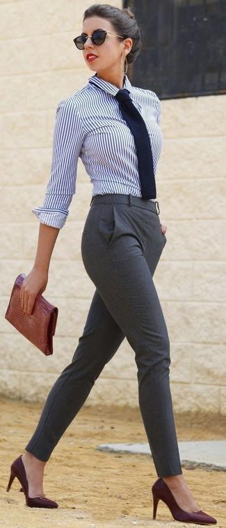 Cómo combinar: camisa de vestir de rayas verticales en blanco y azul marino, pantalones pitillo de rayas verticales grises, zapatos de tacón de cuero burdeos, cartera sobre de cuero con print de serpiente en tabaco