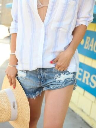 Cómo combinar: camisa de vestir de rayas verticales en blanco y azul, top de bikini de crochet en beige, pantalones cortos vaqueros desgastados azules, sombrero de paja marrón claro