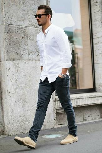 Cómo combinar: camisa de vestir blanca, vaqueros pitillo en gris oscuro, botines chelsea de ante en beige, gafas de sol negras