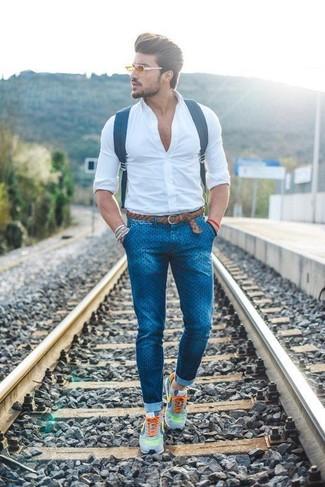 Cómo combinar: camisa de vestir blanca, vaqueros pitillo a lunares azules, deportivas grises, mochila de cuero azul marino