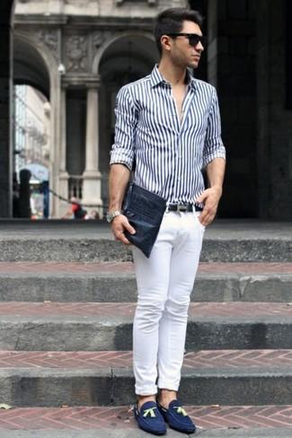Cómo combinar: camisa de vestir de rayas verticales en blanco y azul marino, vaqueros pitillo blancos, mocasín con borlas de ante azul marino, bolso con cremallera de cuero negro