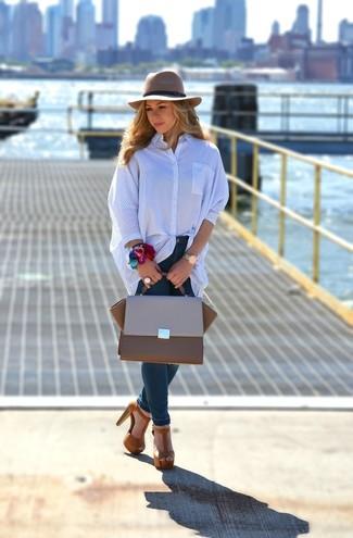 Cómo combinar: camisa de vestir de rayas verticales azul, vaqueros pitillo azul marino, sandalias de tacón de ante marrónes, bolso de hombre de cuero marrón
