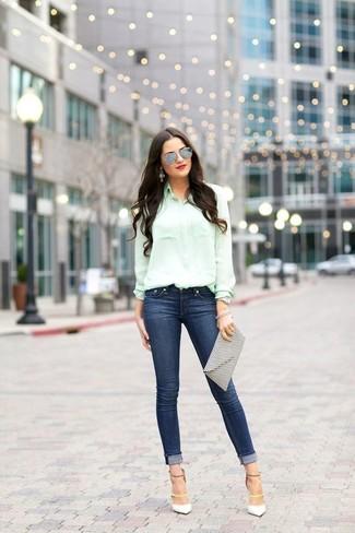 Cómo combinar: camisa de vestir en verde menta, vaqueros pitillo azul marino, zapatos de tacón de cuero blancos, cartera sobre de cuero estampada en blanco y negro