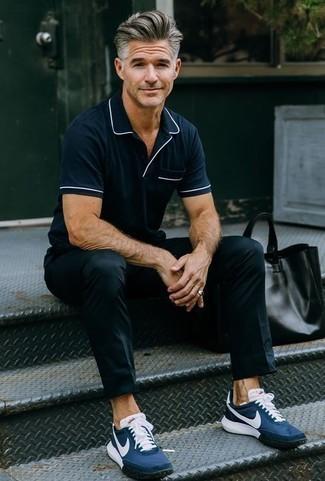 Cómo combinar un pantalón chino negro: Elige una camisa polo azul marino y un pantalón chino negro para un almuerzo en domingo con amigos. ¿Te sientes valiente? Completa tu atuendo con deportivas azul marino.