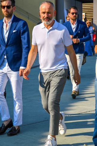 Cómo combinar una camisa polo blanca para hombres de 50 años: Ponte una camisa polo blanca y un pantalón chino gris para un almuerzo en domingo con amigos. Tenis de cuero blancos son una opción excelente para completar este atuendo.