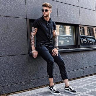 Cómo combinar una camisa polo negra: Intenta combinar una camisa polo negra junto a un pantalón chino negro para un look diario sin parecer demasiado arreglada. Tenis de lona en negro y blanco son una opción incomparable para completar este atuendo.