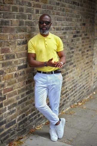 Cómo combinar: camisa polo amarilla, pantalón chino blanco, tenis de cuero blancos, correa de cuero negra