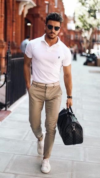Cómo combinar: camisa polo blanca, pantalón chino en beige, tenis blancos, bolsa de viaje de cuero negra