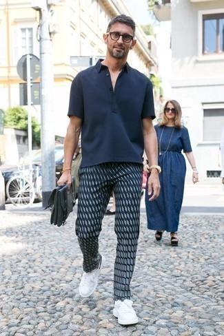 Look de moda: Camisa polo azul marino, Pantalón chino estampado azul marino, Tenis de cuero en blanco y negro, Portafolio de lona azul marino