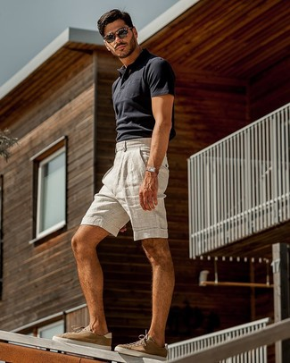 Cómo combinar: camisa polo azul marino, pantalones cortos de lino grises, tenis de ante marrónes, gafas de sol en marrón oscuro