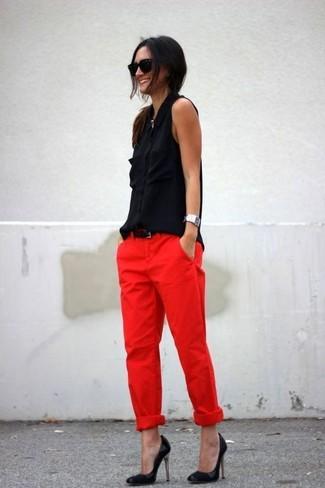 Cómo combinar: camisa sin mangas de seda negra, pantalón chino rojo, zapatos de tacón de cuero negros, correa de cuero negra