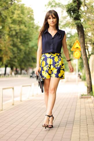 Cómo combinar: camisa sin mangas azul marino, pantalones cortos con print de flores en azul marino y amarillo, sandalias de tacón de cuero negras, cartera sobre de cuero negra