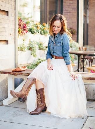 Cómo combinar: camisa vaquera azul, falda larga de tul blanca, botas camperas de cuero marrónes, correa de cuero marrón