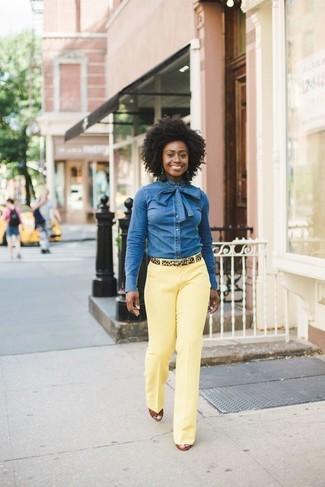 Cómo combinar: camisa vaquera azul, pantalón de vestir amarillo, sandalias con cuña de cuero en tabaco, correa de ante de leopardo marrón claro