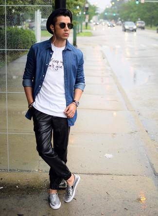 Cómo combinar: camisa vaquera azul, camiseta con cuello circular estampada en blanco y negro, pantalón de chándal de cuero negro, zapatillas slip-on de cuero grises