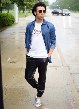 Cómo combinar: camisa vaquera azul, camiseta con cuello circular estampada blanca, pantalón de chándal de cuero negro, zapatillas slip-on de cuero plateadas