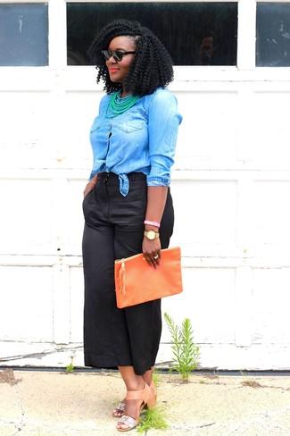 Cómo combinar: camisa vaquera azul, falda pantalón negra, sandalias de tacón de cuero marrón claro, cartera sobre de cuero naranja