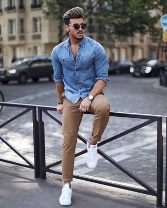 Cómo combinar: camisa vaquera azul, pantalón chino marrón claro, tenis de cuero blancos, gafas de sol negras