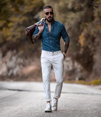 Cómo combinar: camisa vaquera azul, pantalón chino blanco, tenis de cuero blancos, bolsa de viaje de cuero marrón