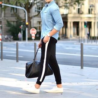 Cómo combinar: camisa vaquera celeste, pantalón de chándal en negro y blanco, tenis blancos, bolsa de viaje de cuero negra