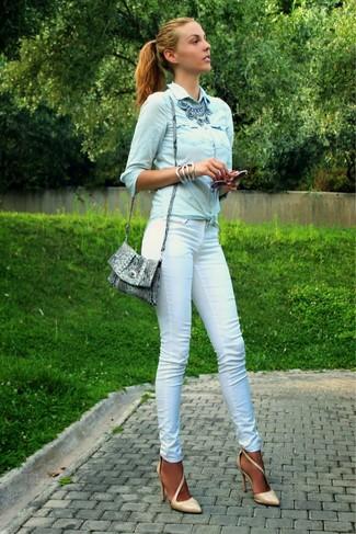 Cómo combinar: camisa vaquera celeste, pantalones pitillo blancos, zapatos de tacón de cuero marrón claro, bolso bandolera de cuero con print de serpiente gris