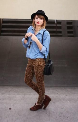 Cómo combinar: camisa vaquera azul, vaqueros pitillo de leopardo marrón claro, botines con cuña de ante en marrón oscuro, bolso bandolera de cuero negro