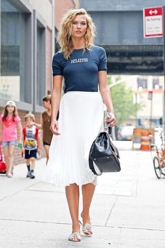 Cómo combinar: camiseta con cuello circular estampada azul marino, falda midi plisada blanca, sandalias planas de encaje blancas, bolso de hombre de cuero negro