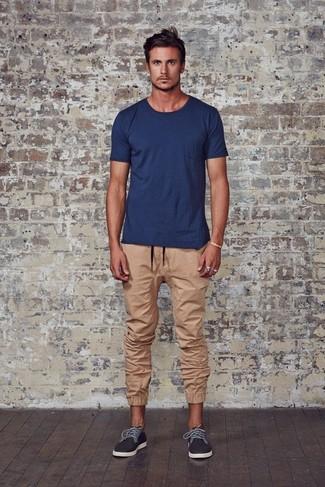 Cómo combinar: camiseta con cuello circular azul marino, pantalón de chándal marrón claro, zapatillas plimsoll en gris oscuro
