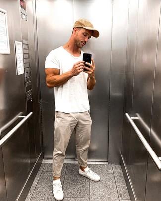 Cómo combinar: camiseta con cuello circular blanca, pantalón chino en beige, tenis blancos, gorra de béisbol marrón claro