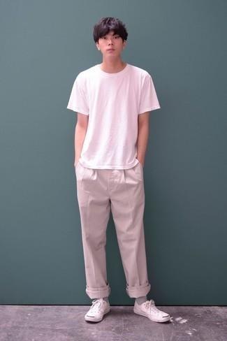 Cómo combinar un pantalón chino en beige para hombres adolescentes: Elige una camiseta con cuello circular blanca y un pantalón chino en beige para un look diario sin parecer demasiado arreglada. Este atuendo se complementa perfectamente con tenis de lona blancos.