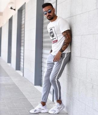 Cómo combinar: camiseta con cuello circular estampada blanca, pantalón chino gris, deportivas blancas, gafas de sol azul marino