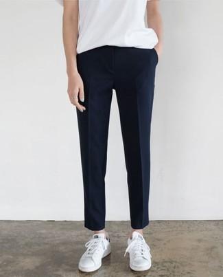 Cómo combinar: camiseta con cuello circular blanca, pantalón de vestir azul marino, tenis de cuero blancos