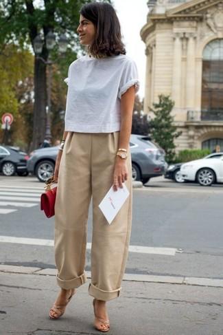 Cómo combinar: camiseta con cuello circular blanca, pantalones anchos marrón claro, sandalias de tacón de cuero en beige, cartera sobre de cuero roja