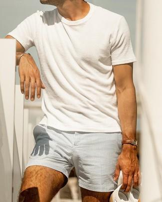 Cómo combinar: camiseta con cuello circular blanca, pantalones cortos de seersucker de rayas verticales celestes, tenis de cuero blancos, reloj de cuero marrón