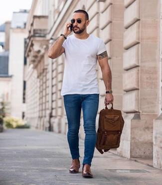 Cómo combinar: camiseta con cuello circular blanca, vaqueros pitillo azules, botines chelsea de cuero marrónes, mochila marrón