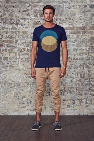 Cómo combinar: camiseta con cuello circular con estampado geométrico azul marino, pantalón de chándal marrón claro, zapatillas plimsoll en gris oscuro